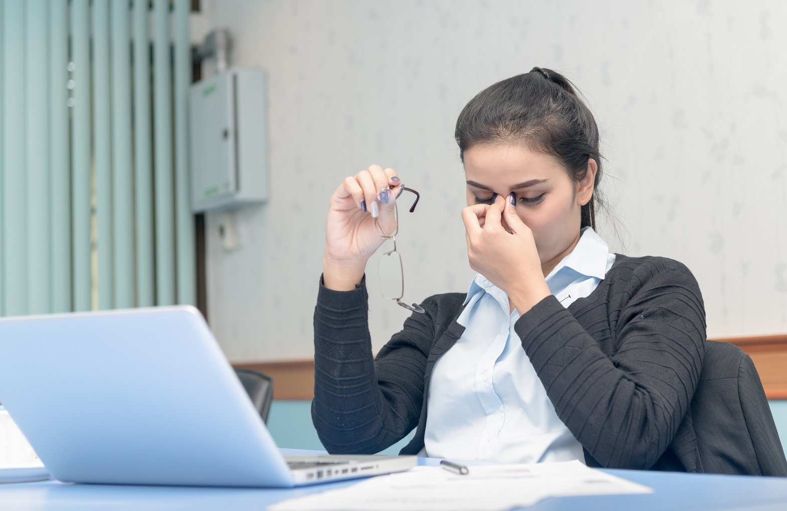 Asian woman got headache from working on computer all day long the effects of wearing wrong prescription glasses