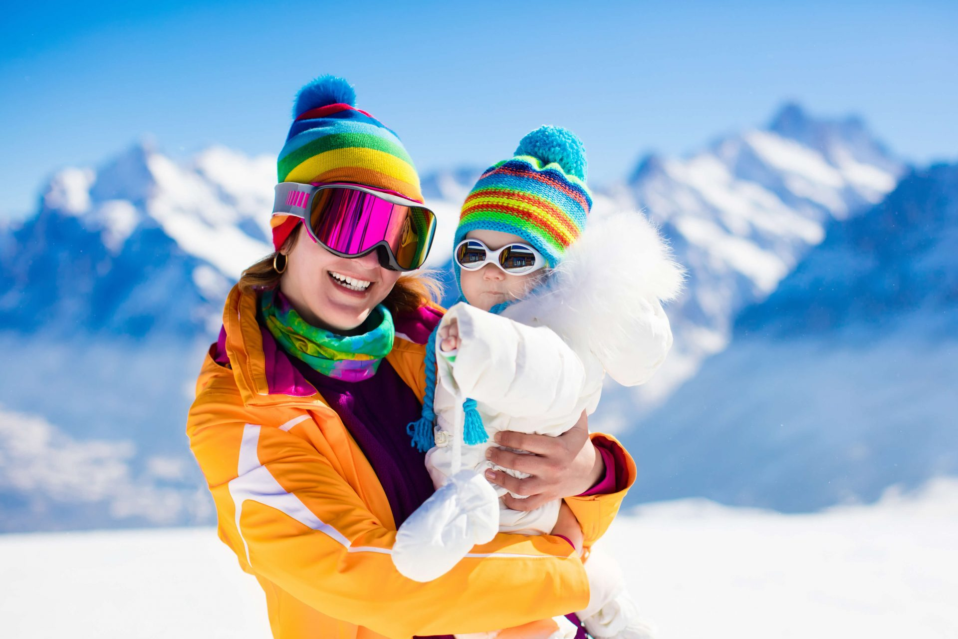 Mother and Child wearing sunglasses in the snowy mountains